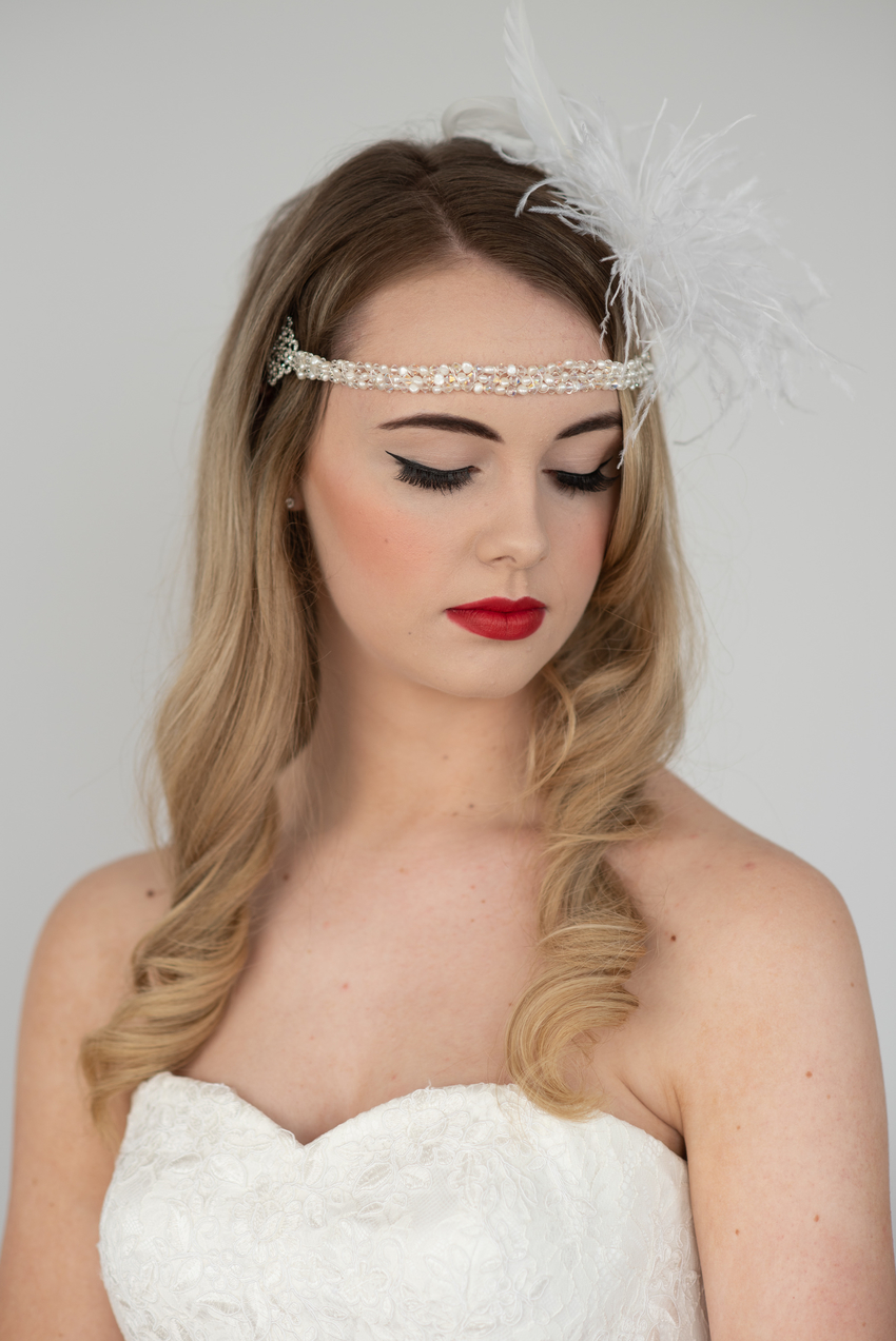 Bride wearing a red lip, blusher, black eye makeup and loose curls in her hair. Wedding hair and makeup done by one of the best wedding hair and makeup artists in Kent, Ellen Dalton