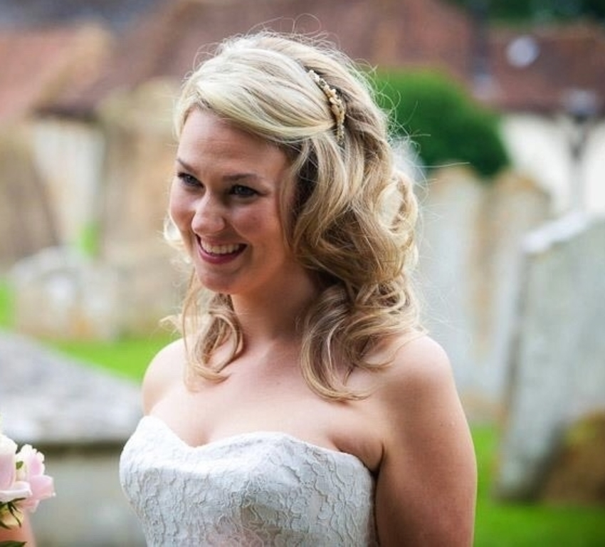 Bride with long, blonde curled hair clipped back, and natural-looking makeup