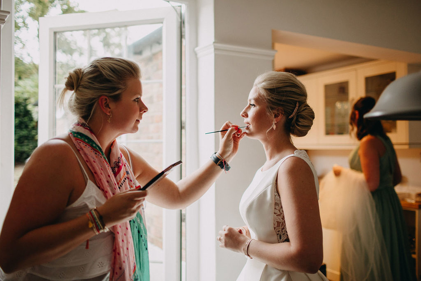One of the best wedding hair and makeup artists in Kent doing her bride's makeup on the morning of her wedding day