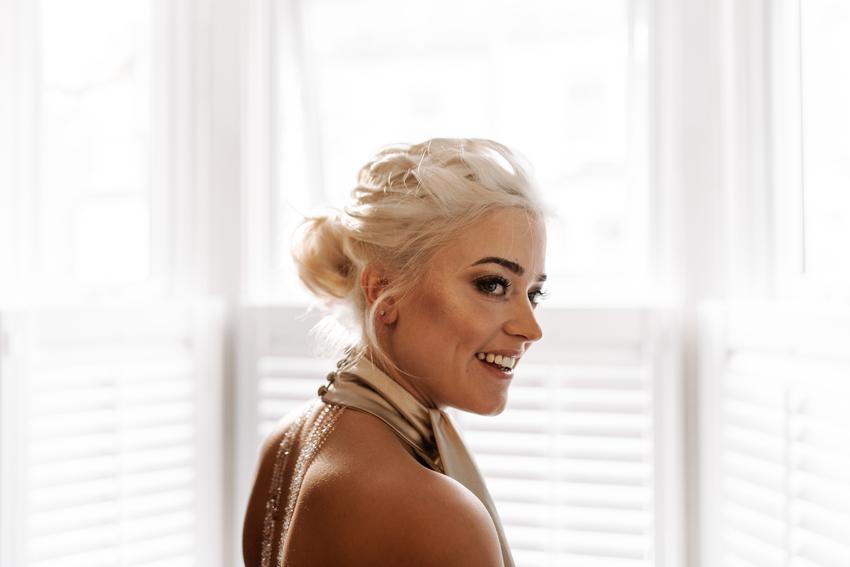 Bleach blonde bride with bronzed cheekbones and a smokey eye