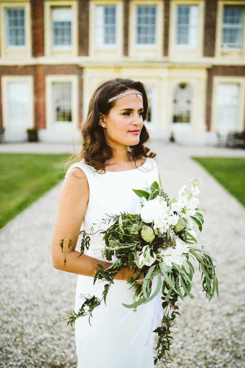 A bride standing at her outdoor wedding. Her wedding hair parted in the middle and slightly curled and a natural makeup look
