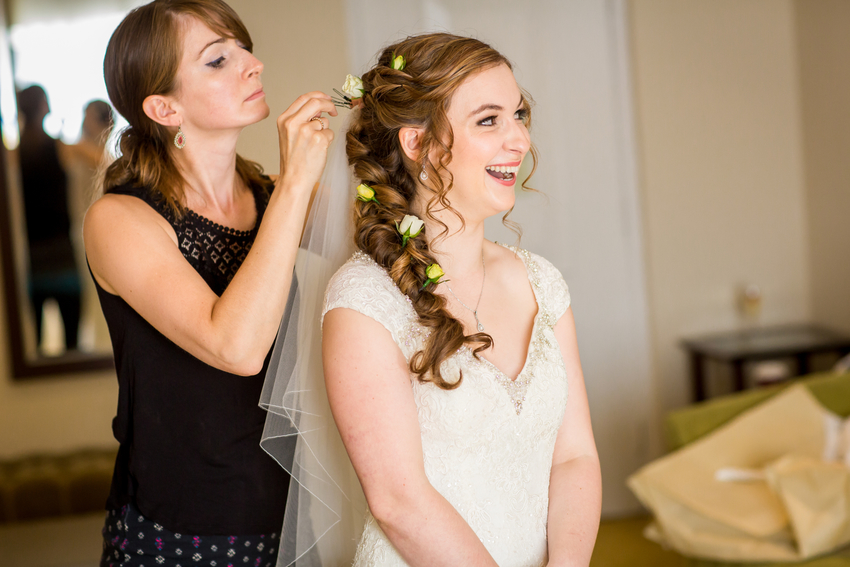 Bride laughs as Kent-based hair and makeup Kirsten finishes her long plait by adding yellow- and cream-coloured roses