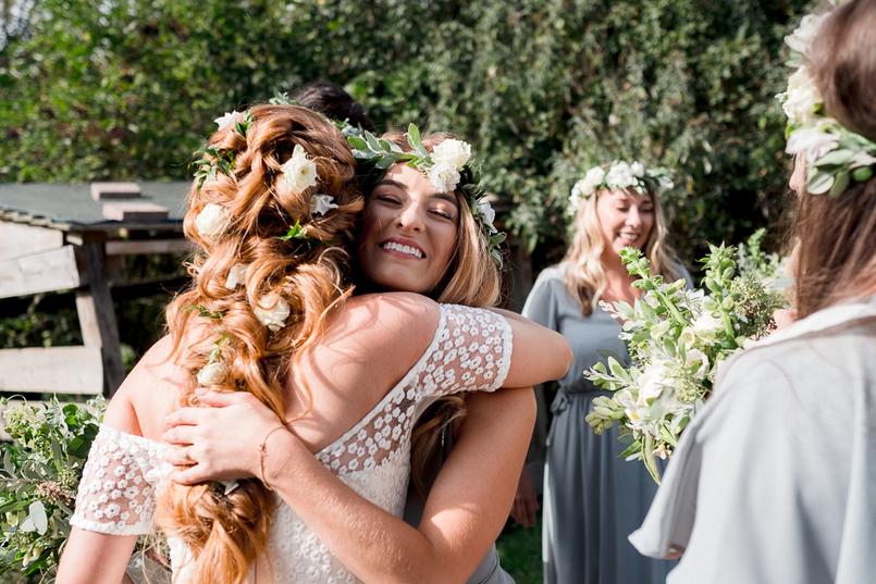 Bride with long, curled hair adorned with roses and leaves hugging her bridesmaid who has a flower crown on
