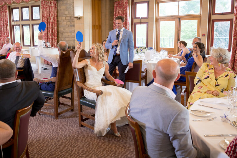 Bride and groom sat back-to-back playing Mr and Mrs on their wedding day