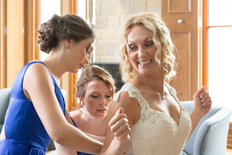 Bridesmaids doing the bride's wedding dress up on her wedding day
