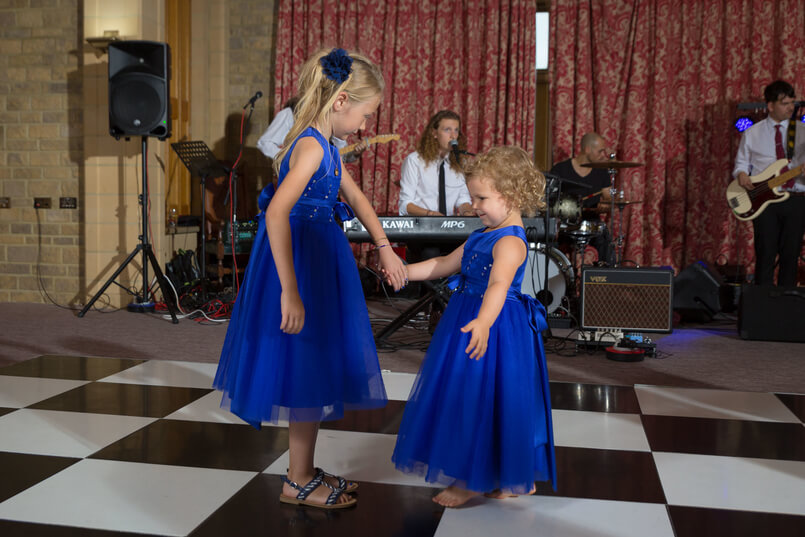 Young bridesmaids wearing blue dresses and dancing together