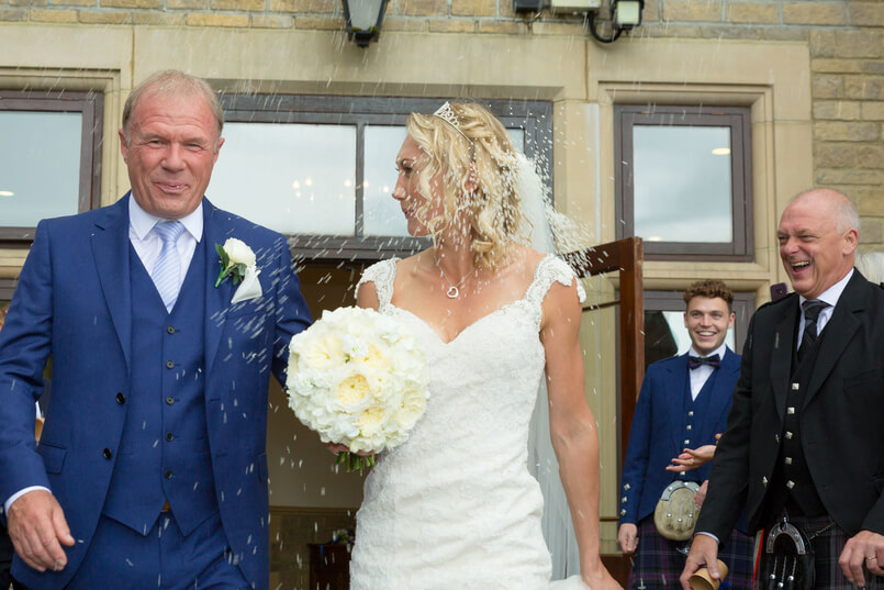 Guests throw rice over bride and groom at French wedding