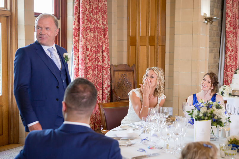 Carine laughing as groom does his wedding speech