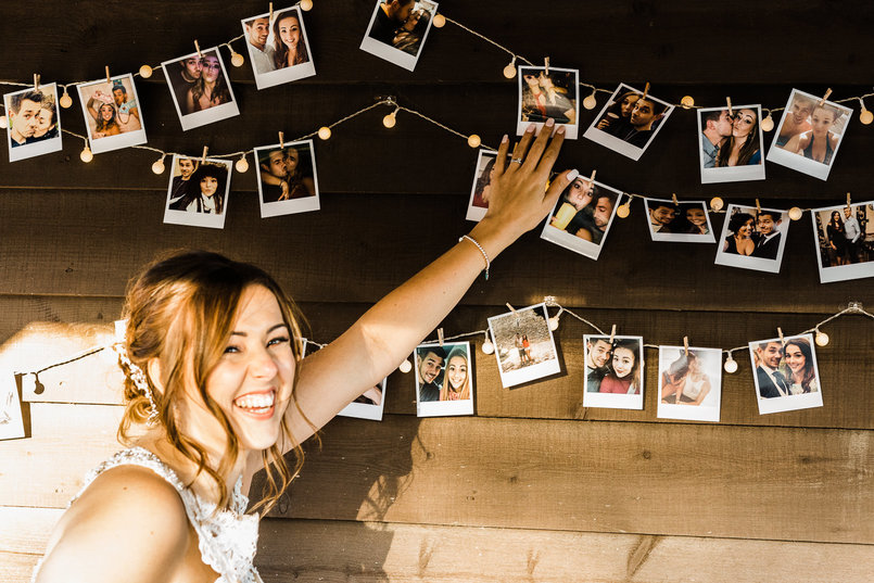 Chilham Bridal bride Yasmin admiring the Polaroid photos that storyboard her relationship with Matt