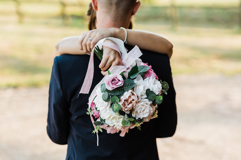 Bride holding her husband over the shoulders, dangling a bunch of pink wedding flowers over the back of him