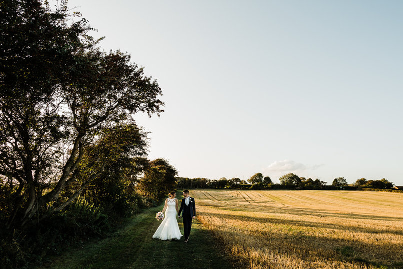 Yasmin and Matt walking through a field in Kent. Photo by Simon Hawkins wedding photography